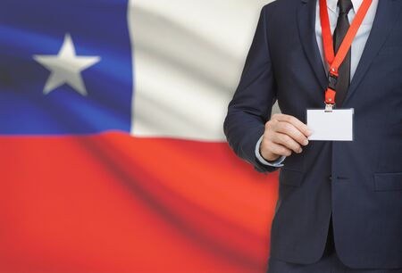 Businessman holding name card badge on a lanyard with a flag on background - Chile Stock Photo