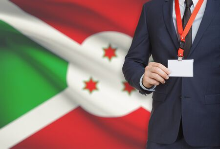 Businessman holding name card badge on a lanyard with a flag on background - Burundi
