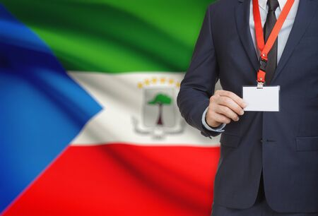 Businessman holding name card badge on a lanyard with a flag on background - Equatorial Guinea Stock Photo