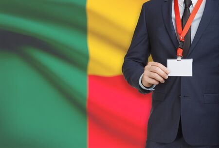 Businessman holding name card badge on a lanyard with a flag on background - Benin
