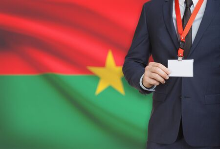 Businessman holding name card badge on a lanyard with a flag on background - Burkina Faso Stock Photo