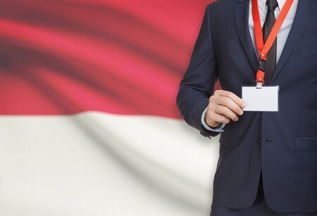 Businessman holding name card badge on a lanyard with a flag on background - Monaco