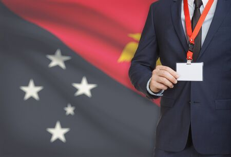 papua new guinea: Businessman holding name card badge on a lanyard with a flag on background - Papua New Guinea