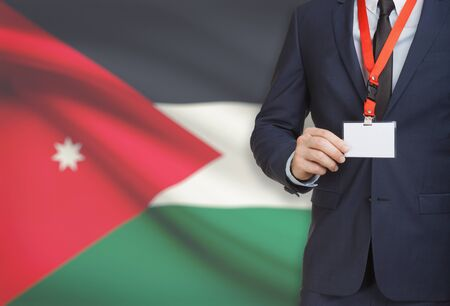 Businessman holding name card badge on a lanyard with a flag on background - Jordan