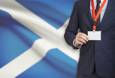 Businessman holding name card badge on a lanyard with a flag on background - Scotland