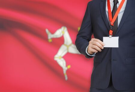 Businessman holding name card badge on a lanyard with a flag on background - Isle of Man Stock Photo