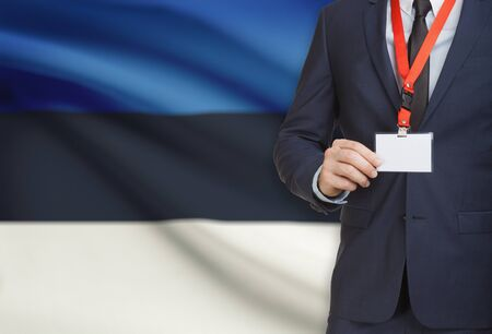 Businessman holding name card badge on a lanyard with a flag on background - Estonia