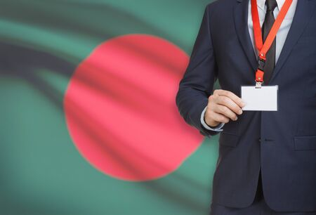 Businessman holding name card badge on a lanyard with a flag on background - Bangladesh