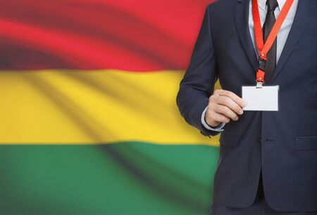 Businessman holding name card badge on a lanyard with a flag on background - Bolivia