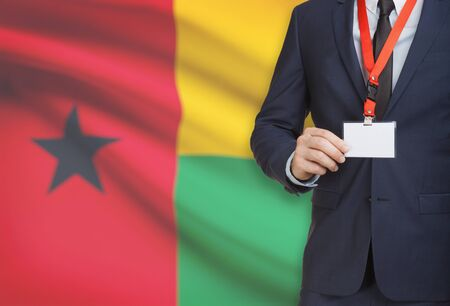 Businessman holding name card badge on a lanyard with a flag on background - Guinea-Bissau