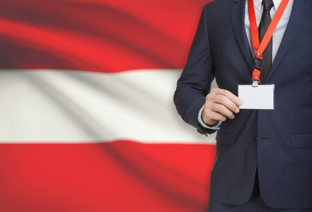 Businessman holding name card badge on a lanyard with a flag on background - Austria