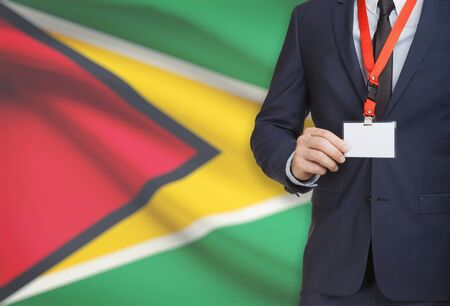 Businessman holding name card badge on a lanyard with a flag on background - Guyana