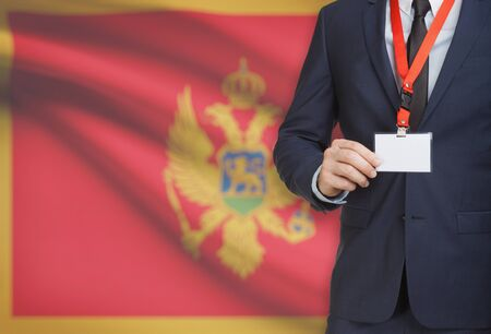 Businessman holding name card badge on a lanyard with a flag on background - Montenegro