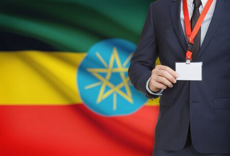 Businessman holding name card badge on a lanyard with a flag on background - Ethiopia Stock Photo