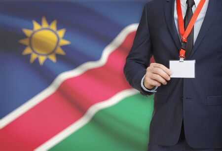 Businessman holding name card badge on a lanyard with a flag on background - Namibia