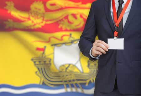 Businessman holding name card badge on a lanyard with Canadian province flag on background - New Brunswick