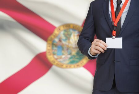 Businessman holding name card badge on a lanyard with US state flag on background - Florida Stock Photo