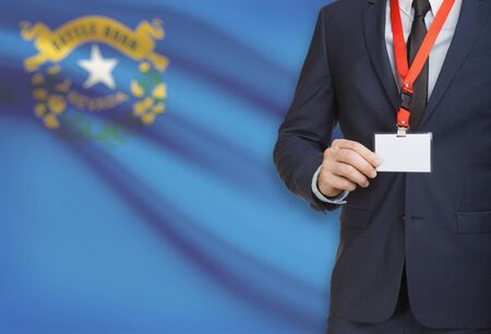 Businessman holding name card badge on a lanyard with US state flag on background - Nevada