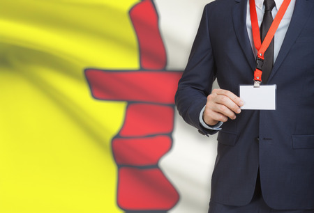 Businessman holding name card badge on a lanyard with Canadian province flag on background - Nunavut