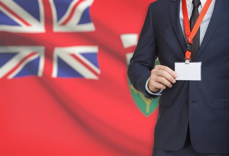 Businessman holding name card badge on a lanyard with Canadian province flag on background - Ontario