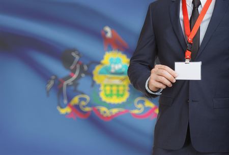 local election: Businessman holding name card badge on a lanyard with US state flag on background - Pennsylvania
