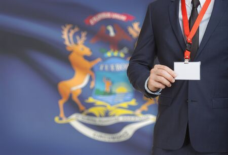 Businessman holding name card badge on a lanyard with US state flag on background - Michigan