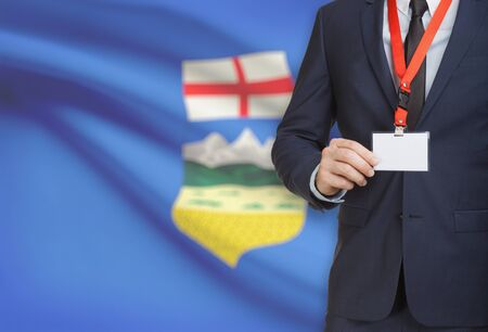 Businessman holding name card badge on a lanyard with Canadian province flag on background - Alberta Stock Photo