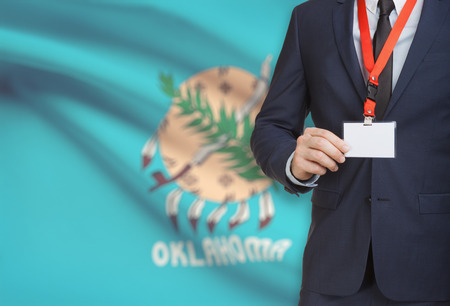 Businessman holding name card badge on a lanyard with US state flag on background - Oklahoma