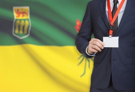 saskatchewan flag: Businessman holding name card badge on a lanyard with Canadian province flag on background - Saskatchewan