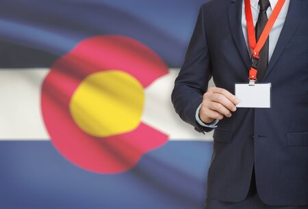 Businessman holding name card badge on a lanyard with US state flag on background - Colorado