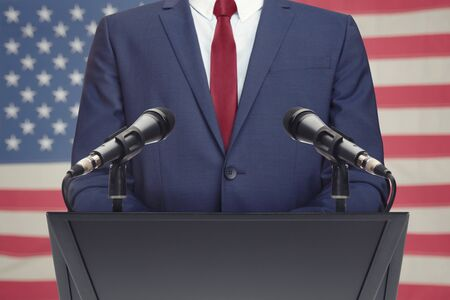 Businessman or politician making speech from behind the pulpit with USA flag on background Stock Photo