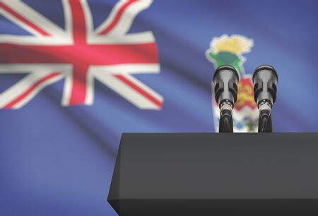 control de calidad: Pulpit and two microphones with a flag on background - Cayman Islands