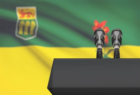 Pulpit and two microphones with Canadian province or territory flag on background - Saskatchewan