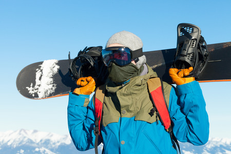 sholders: Male snowboarder holding board behind his sholders at the top of a mountain Stock Photo