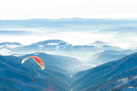 雪の山の非常にピークからの空気にパラグライダーを開始しました。