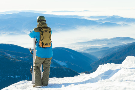 Young snowboarder taking a look at landscape from the top of a mountain