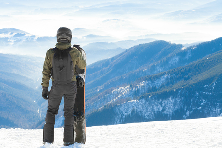 Snowboarder standing next to snowboard thrusted into snow and looking at a beautiful mountain scenery