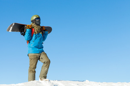Snowboarder in helmet taking a walk at the top of a mountain with beautiful sky on background