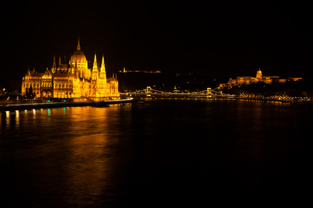 Building of Hungarian Parliament located at the bank of Dunabe river with famous Chain Bridge connecting Buda and Pest in Budapest, Hungary Stock Photo