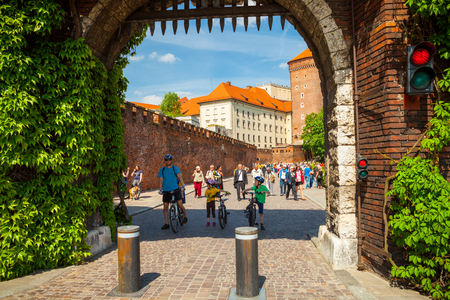 KRAKOW, POLAND - MAY 16, 2015: Tourists passing through Bernardine Gate as main entry to famous historical complex of Wawel Royal Castle and Cathedral in Krakow, Poland - May 16, 2015