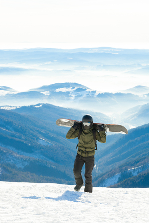 piste: Snowboarder holding snowboard on his sholders and walking to the very top of a snowy mountain