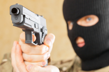 Man in mask holding gun in front of him Stock Photo
