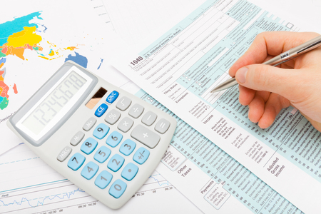 taxpayer: Close up shot of a man filling out 1040 US Tax Form with calculator next to it Stock Photo