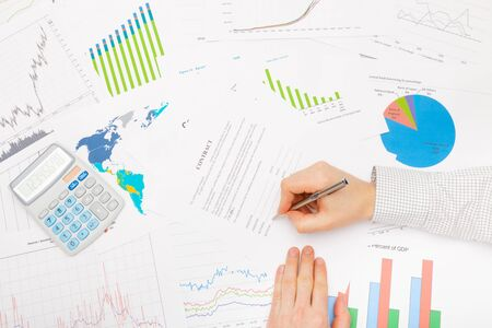 diferent: Businessman at the table with lots of diferent financial data - signing contract