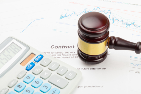 Calculator and wooden judges gavel over some financial documents - close up studio shot
