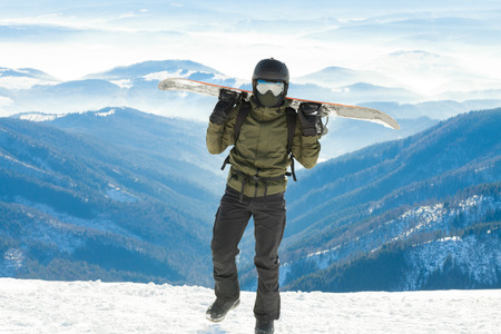 piste: Snowboarder holding snowboard on his sholders and walking to the very top of a mountain