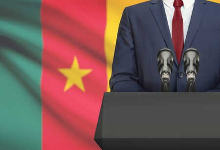 cameroonian: Businessman or politician making speech from behind the pulpit with national flag on background - Cameroon Stock Photo