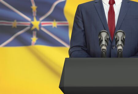 niue: Businessman or politician making speech from behind the pulpit with national flag on background - Niue Stock Photo