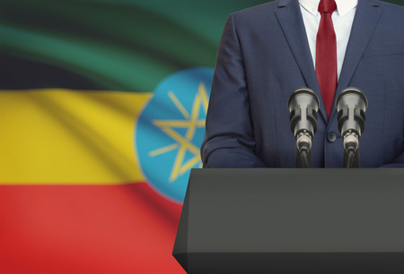 Businessman or politician making speech from behind the pulpit with national flag on background - Ethiopia