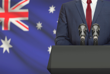 Businessman or politician making speech from behind the pulpit with national flag on background - Australia